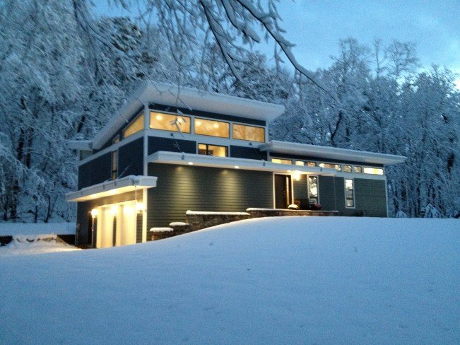 Snow-covered home alight at night