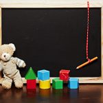 empty blackboard with a vintage generic teddy bear and old wooden blocks
