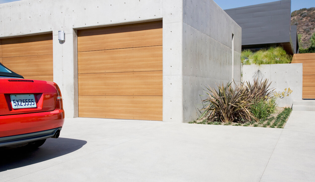 concrete driveway and garage with wooden garage door and partial view of red car parked nearby