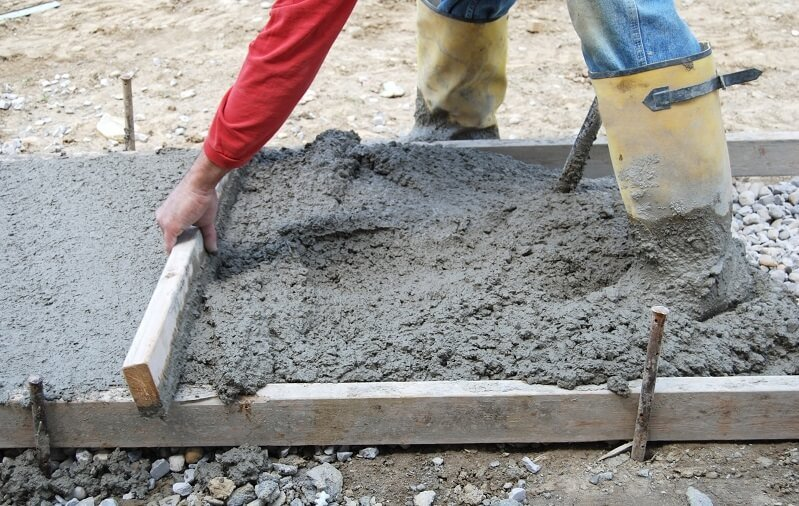 professional installs concrete in a yard