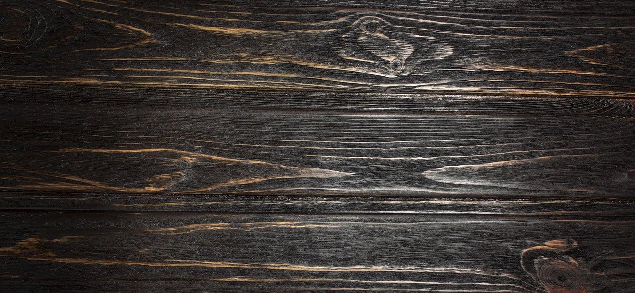 Ebony hardwood flooring texture closeup.