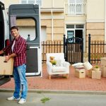 man unloads van outside of his new home
