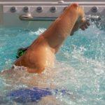 man swimming in endless pool