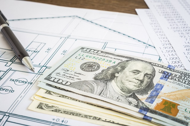 Stack of hundred dollar bills on top of printed construction plans