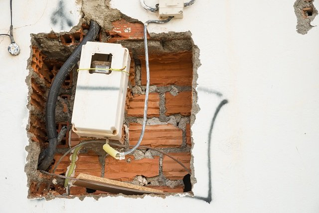 Unfinished wiring and electricity meter on a wall