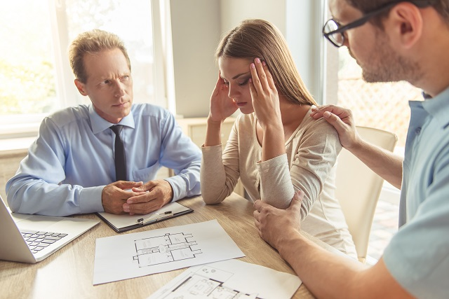 Frustrated couple consulting with professional about home blue prints