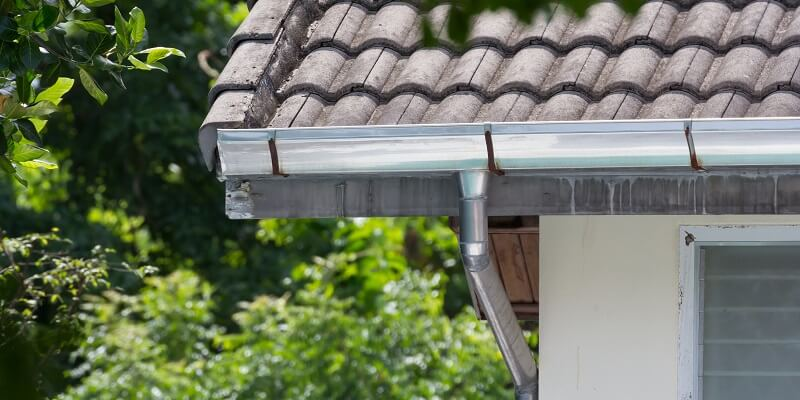 stainless steel gutters on residence with wood shingle roof