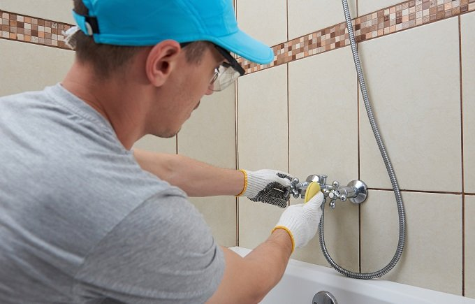 Cleaning bath service. Man in protective glasses polishing faucet