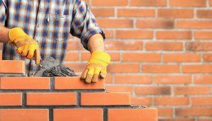 mason lays plaster between brick