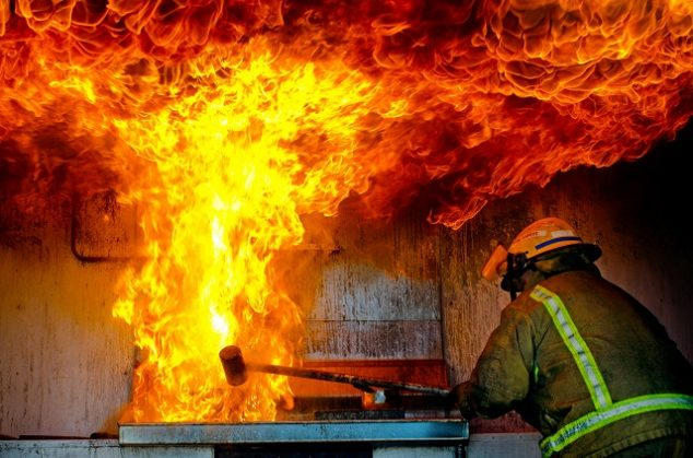 Firefighter putting out a large kitchen fire coming from stove