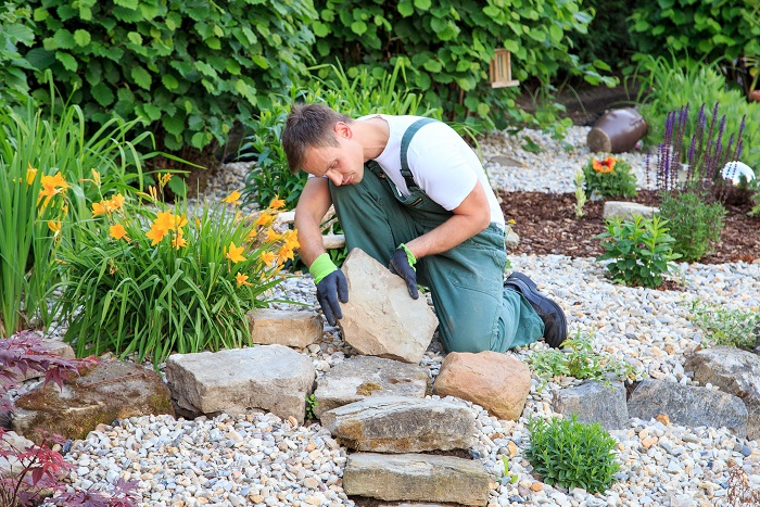 landscaping man works on rock garden