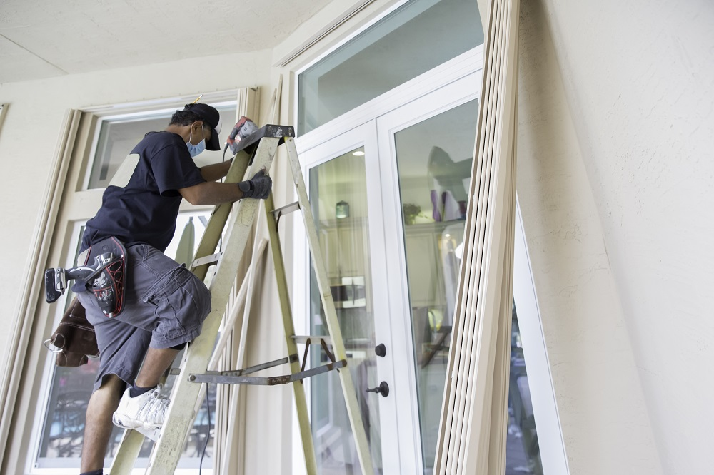Contractor installing hurricane shutters