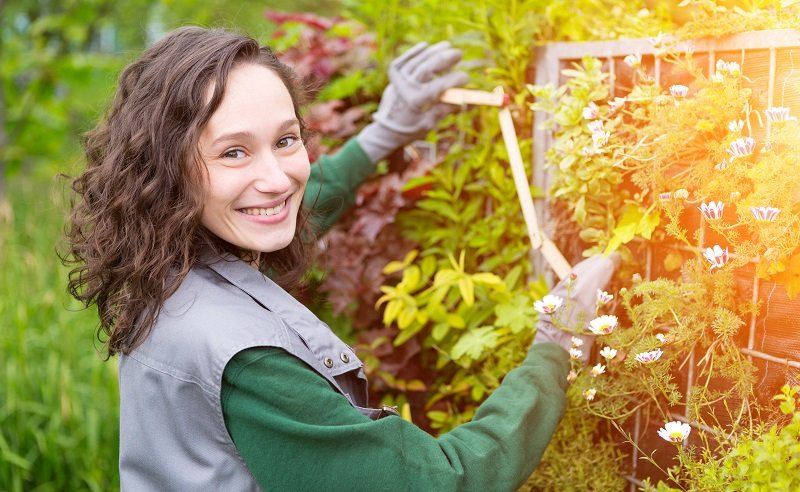 View of a Young attractive landscaper woman working in a yard