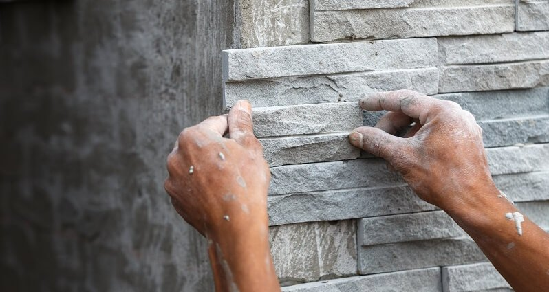 professional installs stone wall