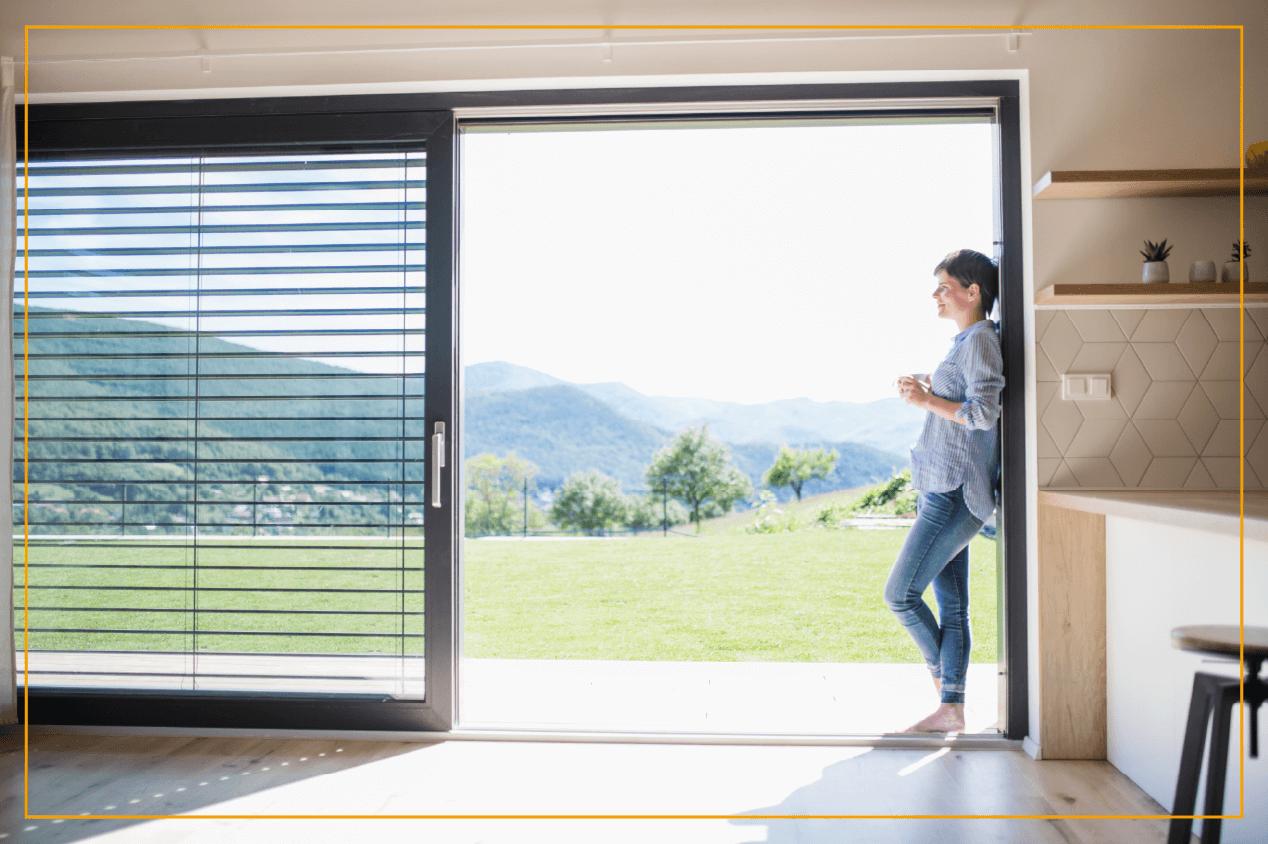 woman looking outside sliding glass window
