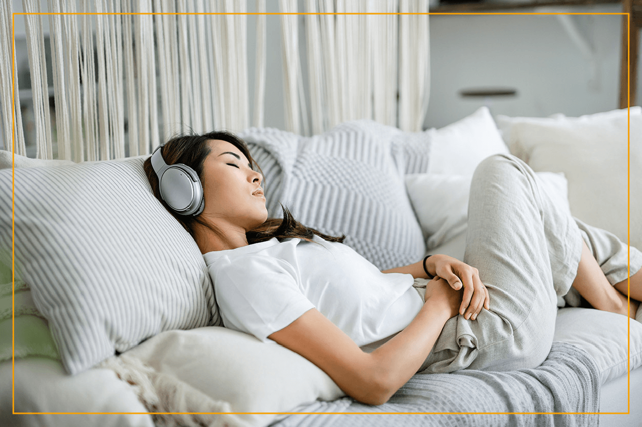 woman relaxed on couch with headphones on