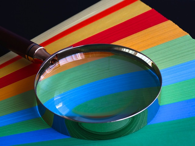 magnifying glass over colorful paper