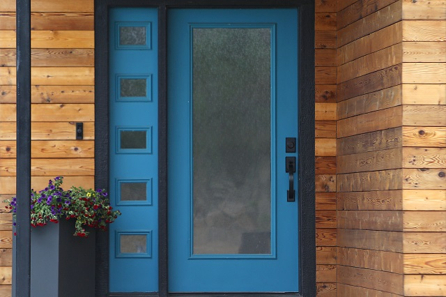 modern front door painted blue with matching transom window and wood siding
