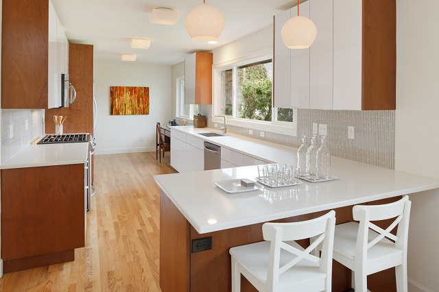 Gorgeous, newly-remodeled kitchen with wood cabinets and floors and white countertop bar