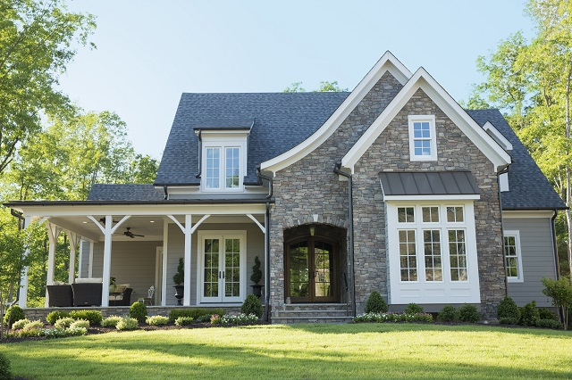 Front elevation of suburban, tudor-style home with partial stone veneer siding