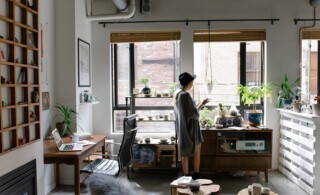 woman in small, crowded but organized condo