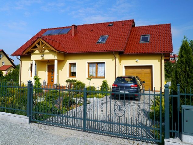yellow house with red roof and aluminum fence