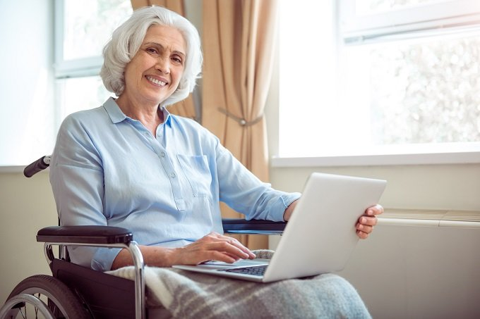 Digitalization. Cheerful and positive senior woman in wheelchair using laptop