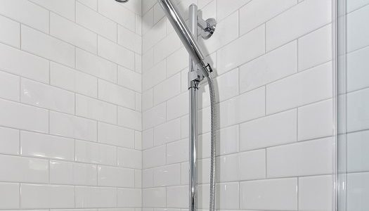 shower head and arm in white tile shower