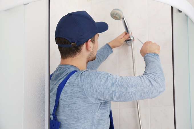 Plumber working in shower stall on shower head