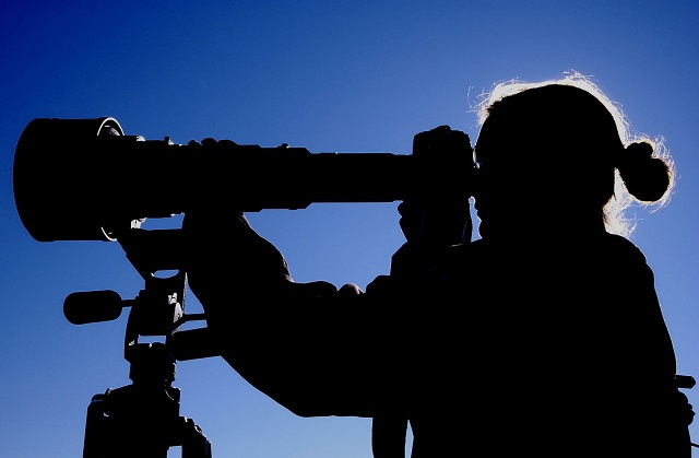 Woman looking through telescope.