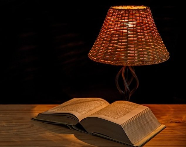 soft light lamp over open book on wooden desk