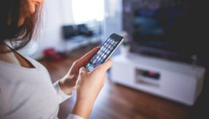 A woman in a grey shirt turns on the television with her smart phone.