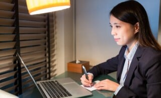 personal assistant writing on the note with laptop computer