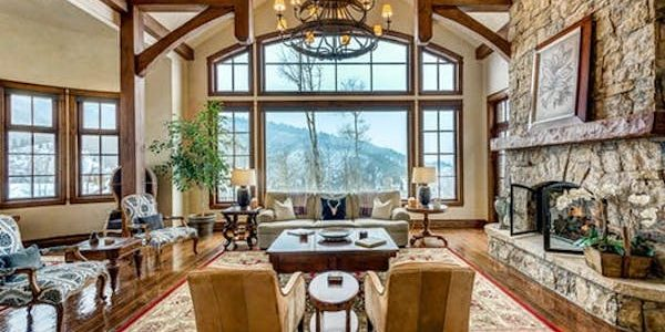 A rustic living room with a view of the Colorado mountains.