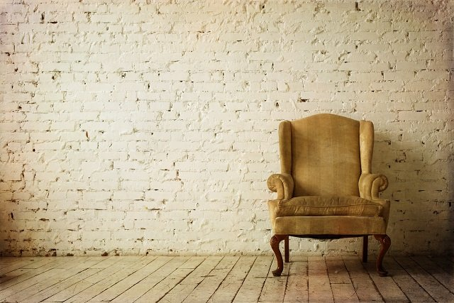 Old Retro Armchair against Blank White Wall.