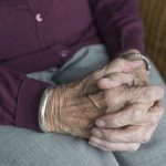 An older gentleman sits in his home with his hands clasped.