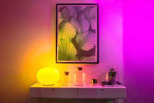 LIFX Smart LED bulb on desk shining vibrant yellow light