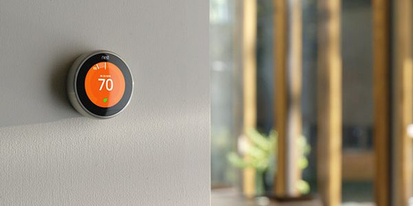 A smart thermostat controls the temperature on a wall.