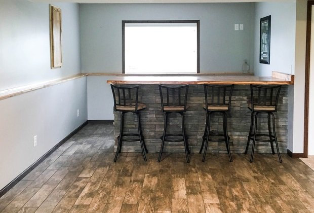 Home bar with stools on reclaimed wood flooring