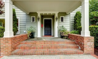 Painted black door in large entrance porch with columns and brick trim