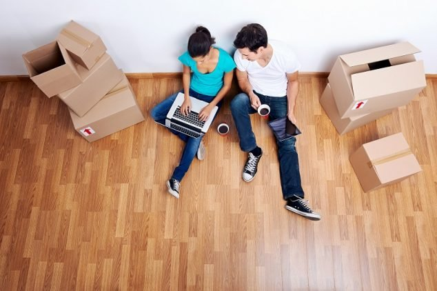 overhead view of couple sitting on floor together using computer wireless internet while moving into new & Engineered Hardwood vs Laminate Flooring (Differences Pros Cons ...