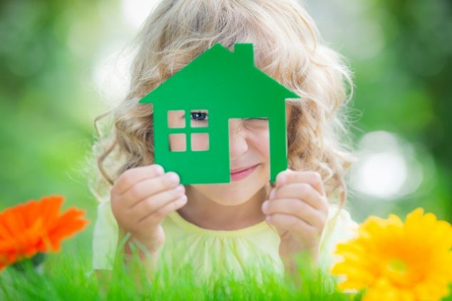 Happy child holding green house in hands with green background.