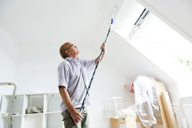 Senior man makes home improvement with new paint
