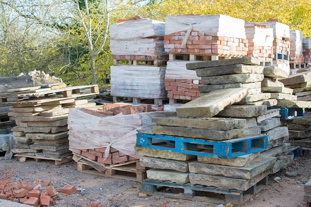 Reclamation yard background: stacks of paving slabs and reclaimed bricks on the pallets