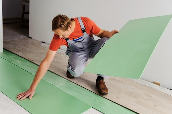 Worker puts the pieces underlayment for subsequent installation of laminate flooring