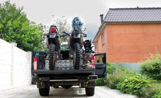 Rear view with two dirt bike motorcycles on the back of the camo truck with safety gear in residential setting.