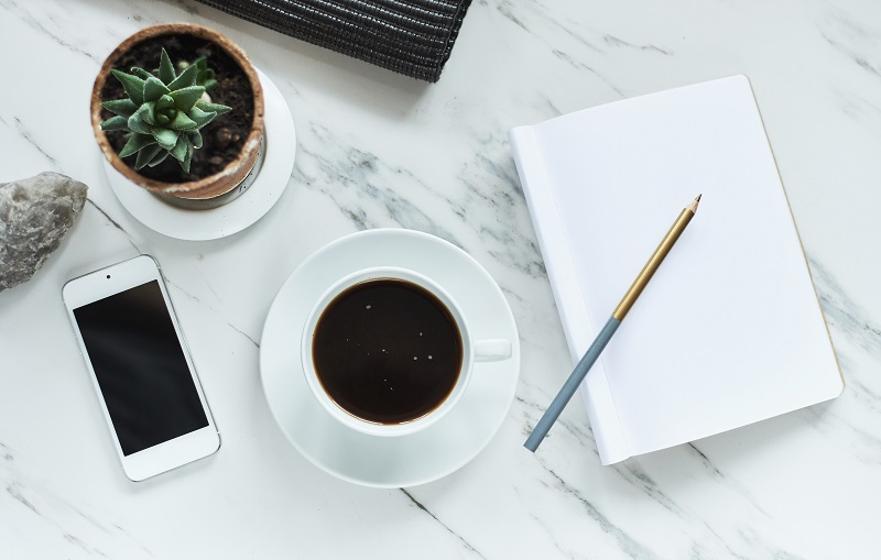 coffee, phone and empty notepad with pencile on marble background. top view