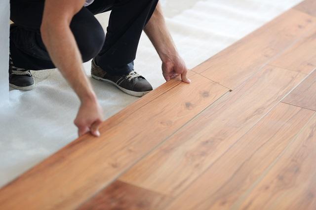 Young woman installing laminate flooring
