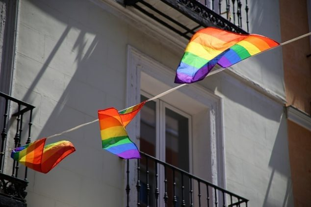 Rainbow flags hanging from the balconies of an old house