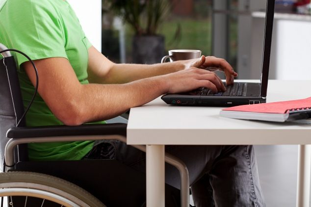 Disabled man writing on laptop